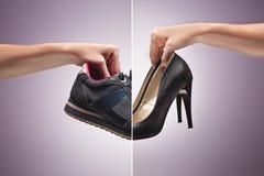 拿着一双老肮脏的运动鞋鞋子的手 免版税图库摄影