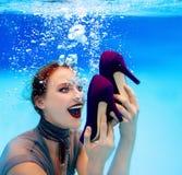 拿着一双鞋的微笑的妇女水下在游泳池 免版税库存图片
