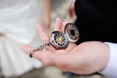 拿着一古色古香的pocketwatch的一个人 免版税库存图片