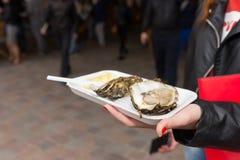 拿着一只唯一新鲜的牡蛎的少妇 免版税库存照片
