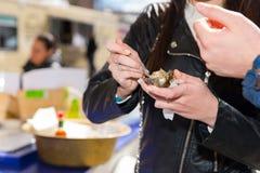 拿着一只唯一新鲜的被打开的牡蛎的女性手 库存照片