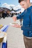 拿着一只唯一新鲜的被打开的牡蛎的年轻人和紧压  库存图片