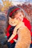 拿着一只大红色猫的小女孩 库存图片