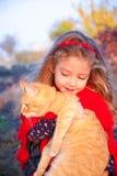 拿着一只大红色猫的小女孩 免版税库存照片