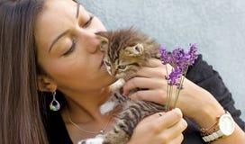 拿着一只小的小猫的美丽的女孩 免版税库存照片