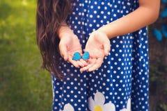 拿着一只小蝴蝶的女孩手 库存图片