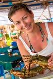 拿着一只未加工的龙虾的女孩 图库摄影