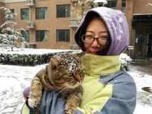 拿着一只猫的小姐在多雪的天 免版税图库摄影