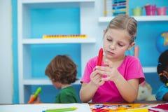 拿着一只红色蜡笔的小女孩 免版税库存图片
