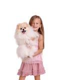 拿着一只美丽的小狗的一个微笑的小女孩,隔绝在白色背景 童年、玩具和孩子概念 免版税库存照片