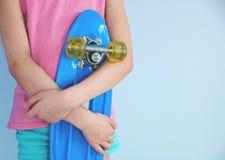 拿着一只蓝色冰鞋的女孩站立对墙壁 免版税库存图片