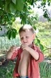 拿着一只蠕动的蠕虫的微笑的小男孩 免版税库存照片