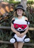 拿着一只被充塞的熊猫的可爱的女孩 图库摄影