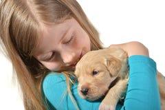 拿着一只金毛猎犬小狗的女孩 库存图片