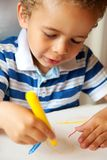 拿着一只黄色蜡笔的幼儿 免版税库存照片