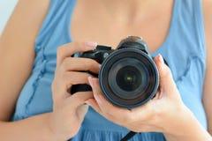 拿着一台专业DSLR照相机的妇女建议她是摄影师 免版税库存图片