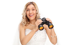 拿着一台双筒望远镜的年轻新娘 免版税库存照片