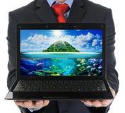 拿着一台开放膝上型计算机的商人 库存照片