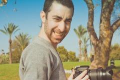 拿着一台数字照相机和微笑对照相机的摄影师 库存照片