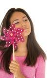 拿着一台桃红色玩具风车的美丽的拉丁美州的青少年的女孩 免版税库存图片