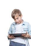 拿着一台棕色片剂个人计算机的一件蓝色衬衣的逗人喜爱的白肤金发的男孩 库存图片