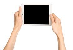拿着一台白色片剂接触计算机的手 免版税库存图片