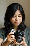 拿着一台老影片照相机的妇女 免版税库存照片