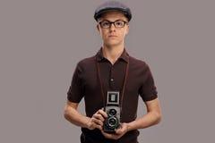 拿着一台老照相机的葡萄酒成套装备的十几岁的男孩 免版税库存图片