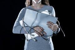拿着一台膝上型计算机和缆绳在计算机瘾概念的一名结束工作的妇女的特写镜头 库存图片