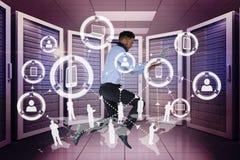 拿着一台计算机和图表的商人在服务器屋子里 图库摄影