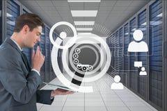 拿着一台计算机和图表的商人在服务器屋子里 库存图片