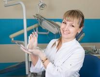 拿着一台医疗仪器的美丽的白肤金发的妇女牙医 牙科设备在背景中 免版税库存图片