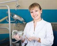 拿着一台医疗仪器的美丽的白肤金发的妇女牙医 牙科设备在背景中 库存图片