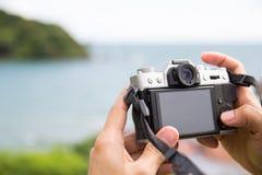 拿着一台mirrorless数字照相机的手为做准备拍照片 图库摄影