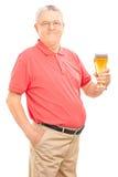 拿着一品脱啤酒的快乐的前辈 免版税库存图片