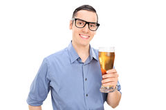 拿着一品脱啤酒的快乐的年轻人 免版税图库摄影