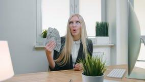 拿着一团现金的微笑的女商人 美好的愉快的白肤金发的女性开会在工作场所的办公室有计算机的 影视素材
