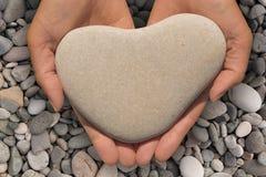 拿着一块心形的石头的女性手 免版税库存图片