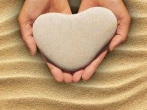 拿着一块心形的石头的女性手 库存照片