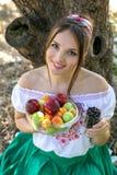 拿着一块板材用果子和一杯的美丽的女孩无核小葡萄干 免版税图库摄影