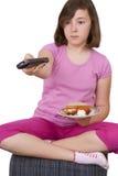 拿着一块板材用食物和电视的十几岁的女孩遥控 库存照片