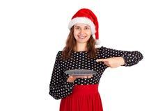 拿着一块空的板材的可爱的女孩把一个手指指向她和显示赞许为准备新年假日 emot 库存图片