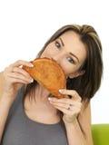 拿着一块被烘烤的康瓦尔郡菜肉烘饼的可爱的少妇 免版税库存照片
