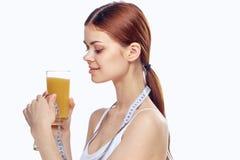 拿着一块玻璃用汁液和测量磁带,饮食的少妇 免版税库存照片