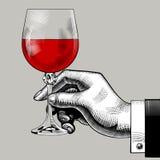 拿着一块玻璃用红葡萄酒的手 免版税库存照片