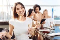 拿着一块玻璃用香槟的愉快的兴高采烈的妇女 免版税库存图片