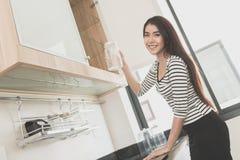 拿着一块玻璃的美丽的少妇在一个现代厨房里 免版税库存图片