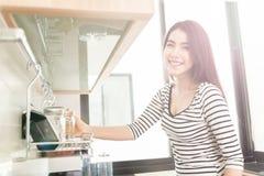 拿着一块玻璃的美丽的少妇在一个现代厨房里 库存图片
