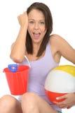 拿着一幅桶和小铲有海滩球的一个愉快的激动的少妇的画象 免版税库存照片