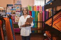 拿着一张剪贴板的微笑的妇女在她的织品商店 库存图片
